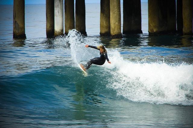 Surfeuse surfant sur les vagues de la plage Manhattan à Los Angeles